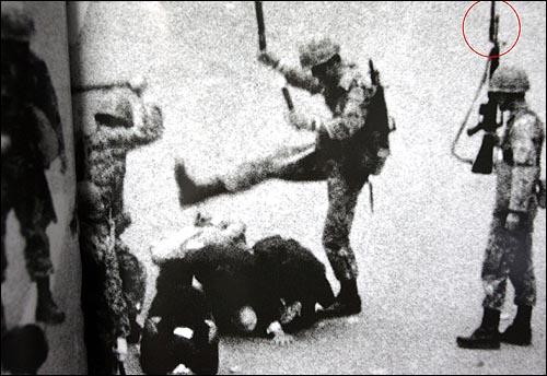 역시 신복진 <전남일보> 사진부 기자가 80년 5월 18일 촬영한 사진. 도망치다 쓰러진 시민을 곤봉으로 내려치고 군화발로 짓밟고 있는 뒤쪽으로 한 공수부대원의 M16소총에 대검이 뚜렷이 보인다.(붉은 색 원) 5.18기념재단이 펴낸 <오월, 우리는 보았다 - 계속되는 오일팔(1979.2.25-2004.5.18)>에서 발췌. 역시 신복진 <전남일보> 사진부 기자가 80년 5월 18일 촬영한 사진. 도망치다 쓰러진 시민을 곤봉으로 내려치고 군화발로 짓밟고 있는 뒤쪽으로 한 공수부대원의 M16소총에 대검이 뚜렷이 보인다.(붉은 색 원) 5.18기념재단이 펴낸 <오월, 우리는 보았다 - 계속되는 오일팔(1979.2.25-2004.5.18)>에서 발췌.